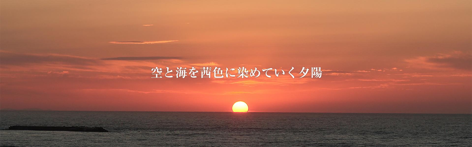 空と海を茜色に染めていく夕陽